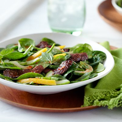 Shaking beef salad with baby spinach and mango