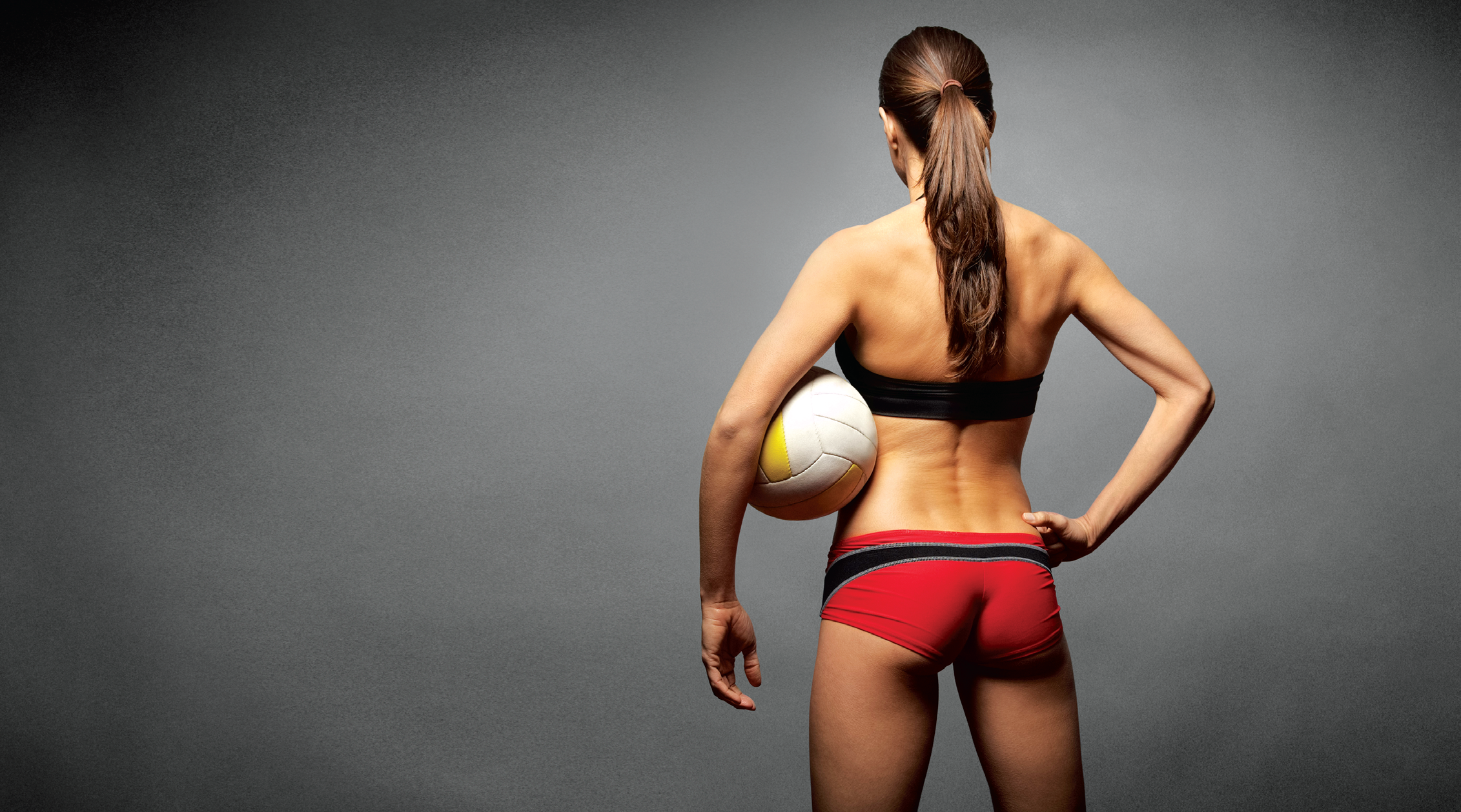 fit woman standing with a volleyball
