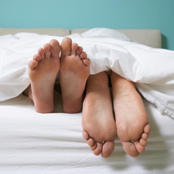 A couple in bed with their feet showing