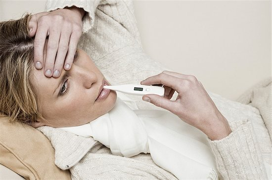 sick woman taking her temperature, thermometer