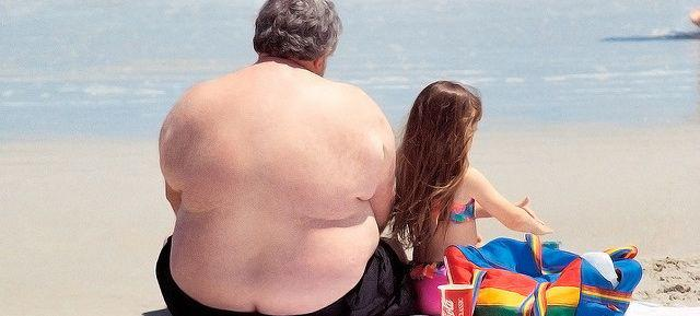 obese man with little girl on beach, ocean water