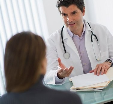 doctor talking to woman patient in office