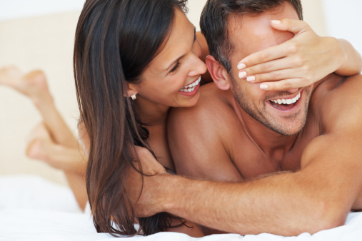 man and woman, couple playful in bed, smiling and laughing