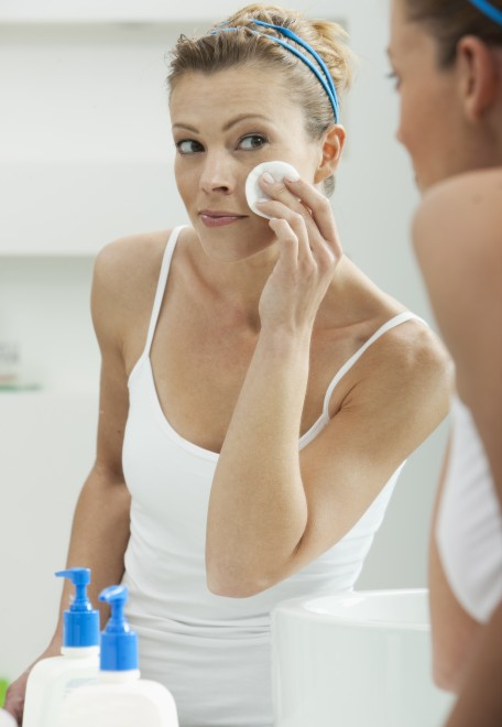 woman with cotton pad, cleaning face in bathroom looking into mirror