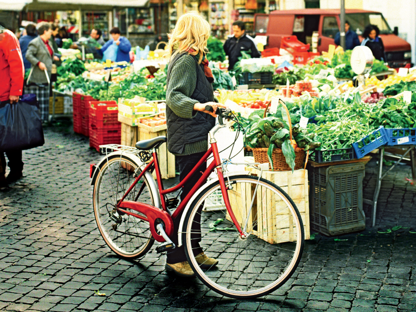A woman standing with a red bicycle looking at vegetables in farmers' market