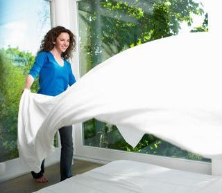 Woman shaking out white sheets