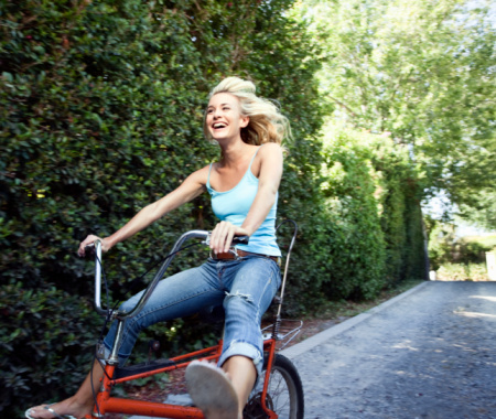 blonde girl riding red bike happy with legs out