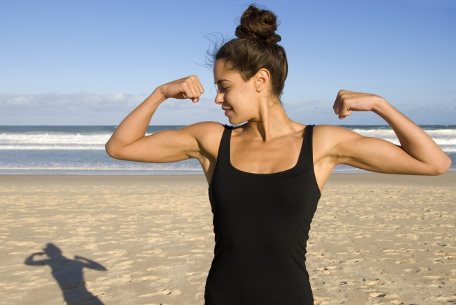 woman showing biceps standing on beach, strength, fitness