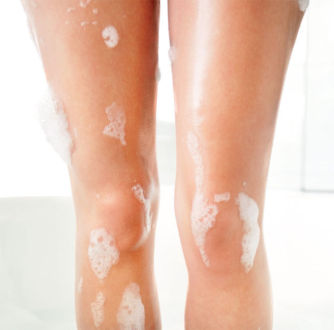 bare legs with soap suds in shower