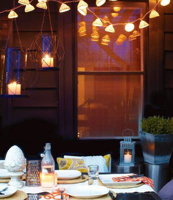 outdoor dining with hanging lights and candles in evening