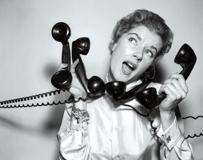 A black and white photo of a woman trying to answer too many phones at once