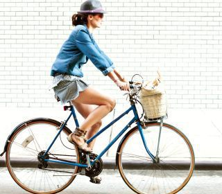 Woman on Bike with Basket Biking Past Wall