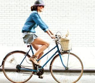 Woman on Bike with Basket Biking Past Wall