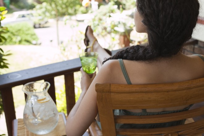 woman brunette relaxing on porch drinking