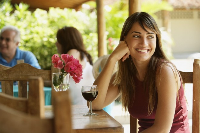 Woman drinking wine in a cafe