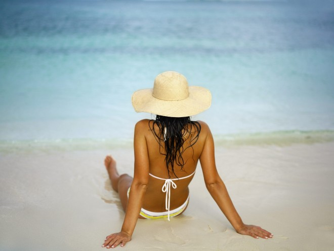Woman lying on the beach with a sun hat on