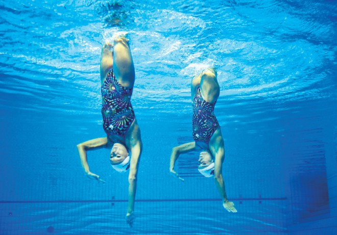 two women in pool underwater synchronized swimming
