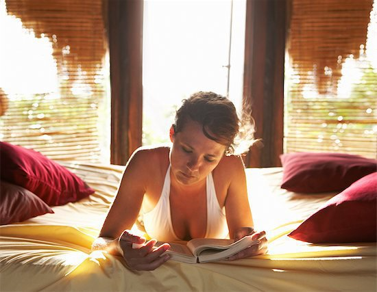 woman on bed reading book, vacation, tropical