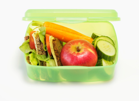 clear green lunch box with sandwich, carrots and apple fruit