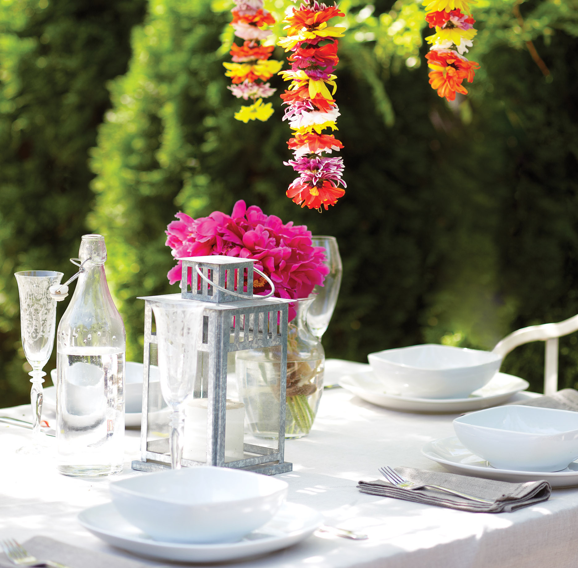 Outdoor table with hanging flowers, white dishware, champagne flutes, flower garlands, backyard party, dinner party
