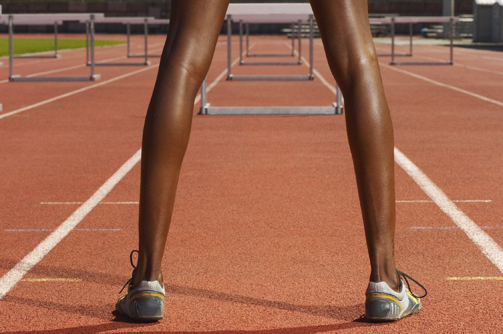 Woman standing on a track before hurdles