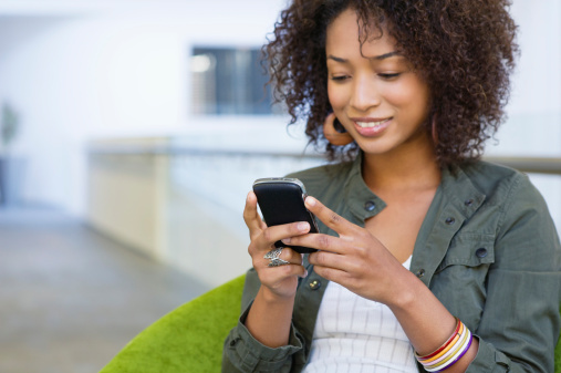 African-american woman looking at phone and smiling