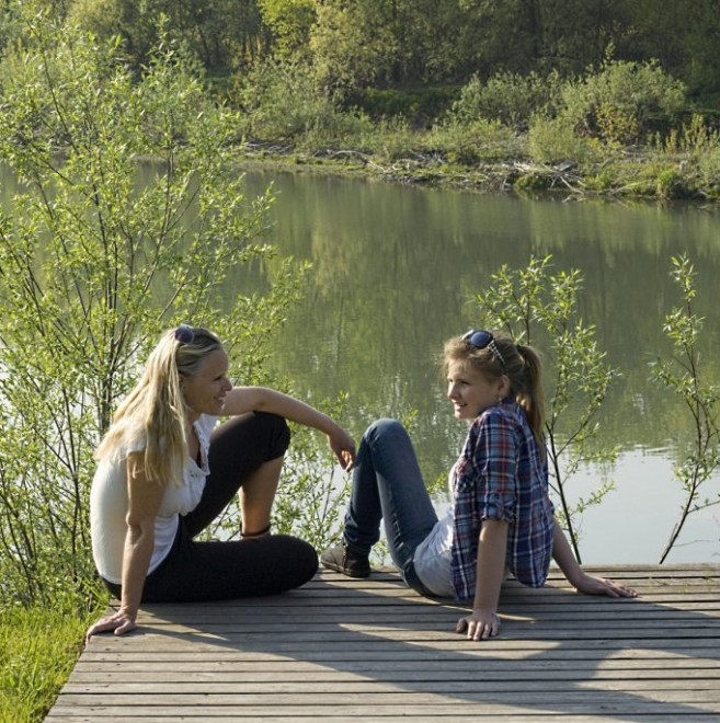 Mother and daugther talking by a lake