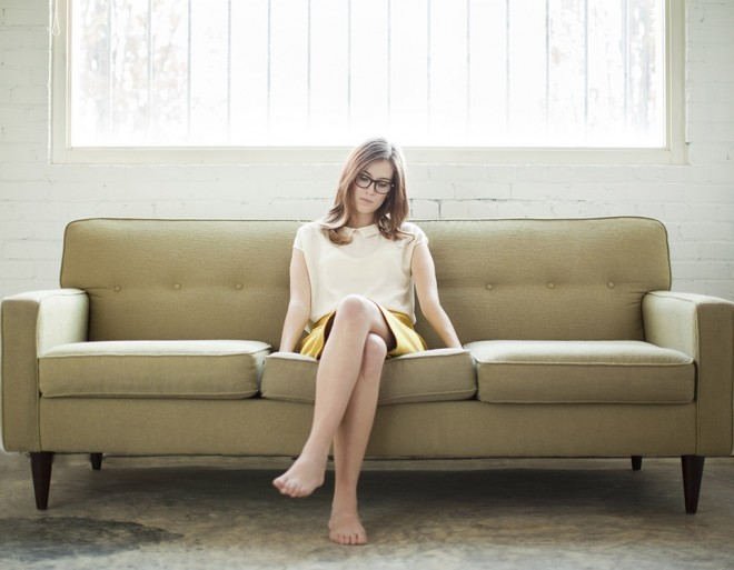 Woman sitting with crossed legs and glasses