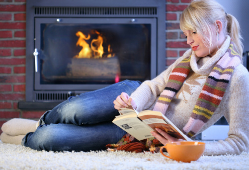 blonde woman reading book by fireplace