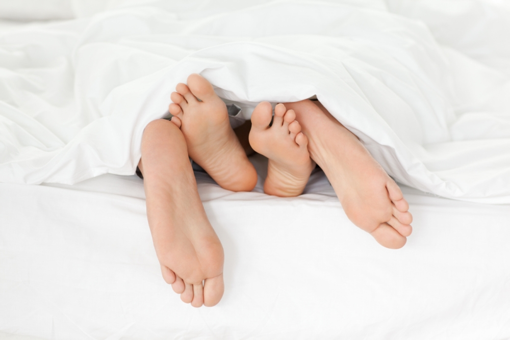 Couple in bed, feet showing