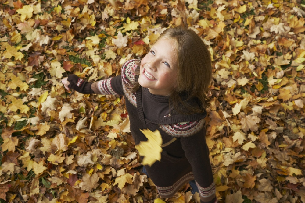 Young girl playing in the autumn leaves