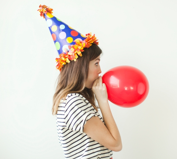 Young woman blowing up a balloon wearing a party hat