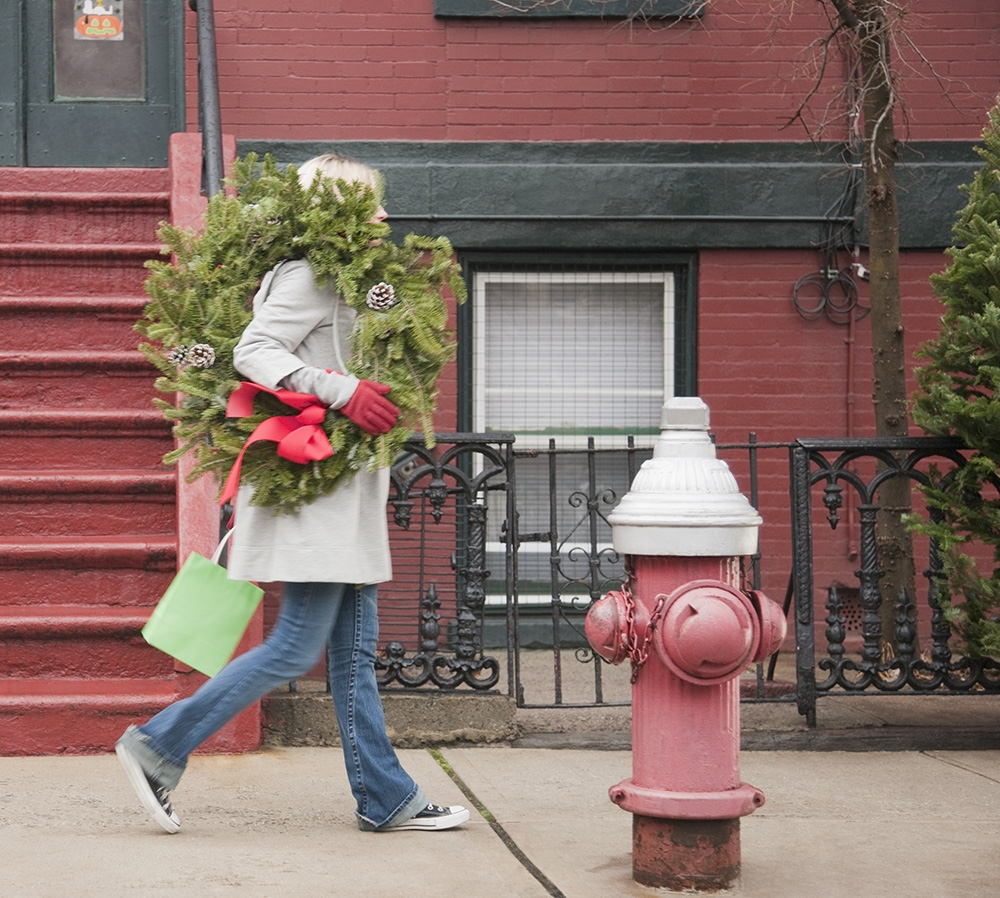 Woman walking with Christmas wreath on the sidewalk