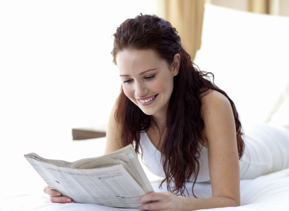 Woman with long hair reading the paper on a bed