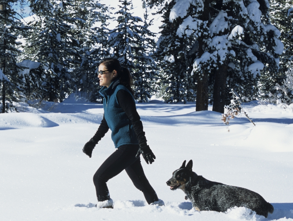 Woman walking in the snow with her dog