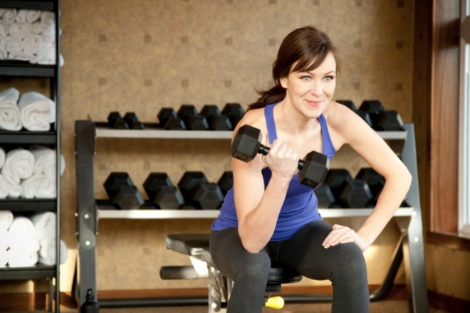 Woman at the gym lifting weights, exercising
