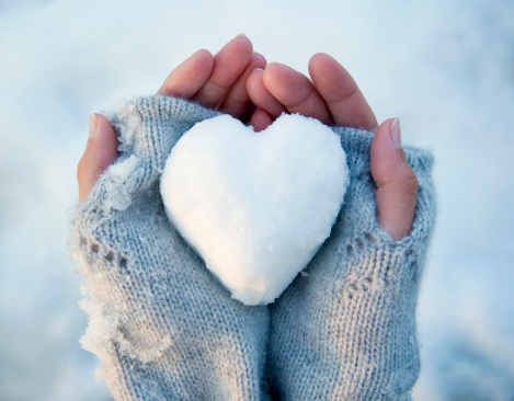 snow-shaped heart in handmittens winter