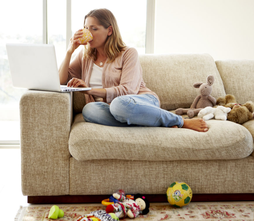 Woman sitting on her couch with laptop
