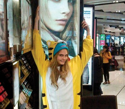 Supermodel Cara Delevingne in her Japanese Kigurumi tiger onesie below her Burberry ad