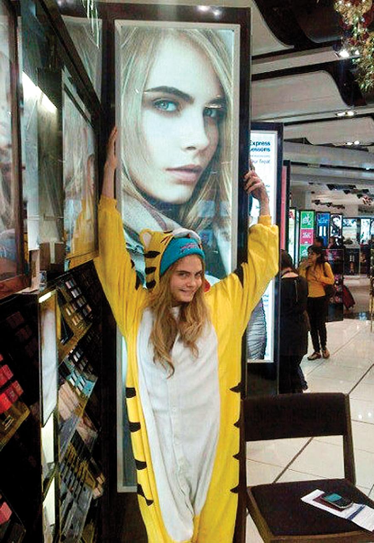 Supermodel Cara Delevingne in her Japanese Kigurumi tiger onesie below her Burberry ad