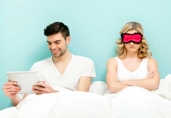 Couple in bed. Wife angry, husband absorbed with his digital tablet.