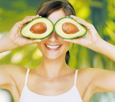 Young woman holding halved avocado over eyes, smiling, close-up