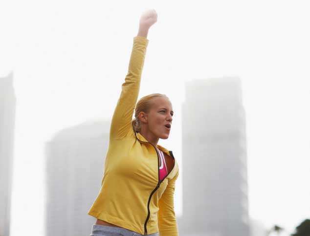 Woman in city with arms raised