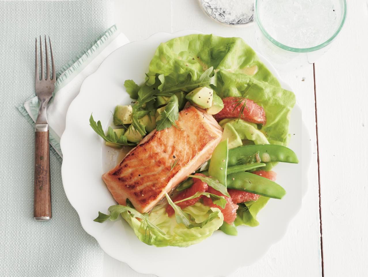 Seared salmon fillet with butter lettuce, snow pea, grapefruit and avocado salad on a plate.