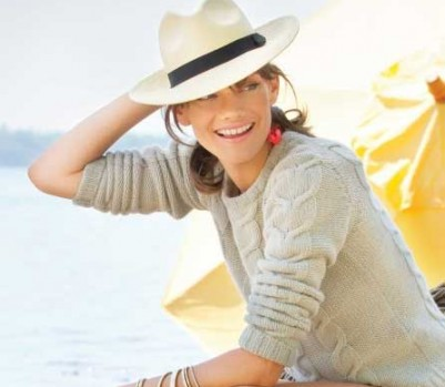 A young woman sitting on the beach with a hat on