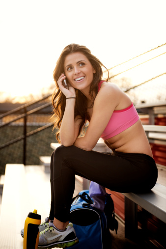 Woman Sitting In Sports Bra on The Phone
