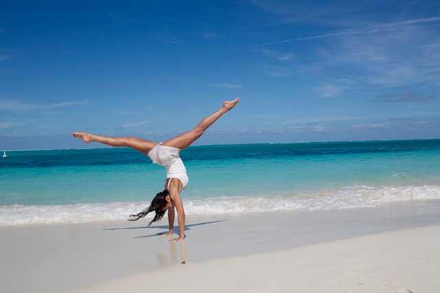 A woman on the beach doing a hand stand inversion