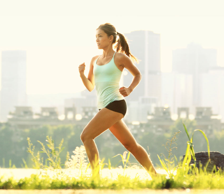 A young fit woman goes for a run on a city pathway