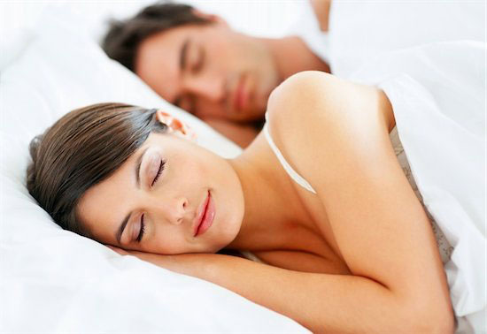 Closeup of a beautiful young lady sleeping on the bed with her husband in background