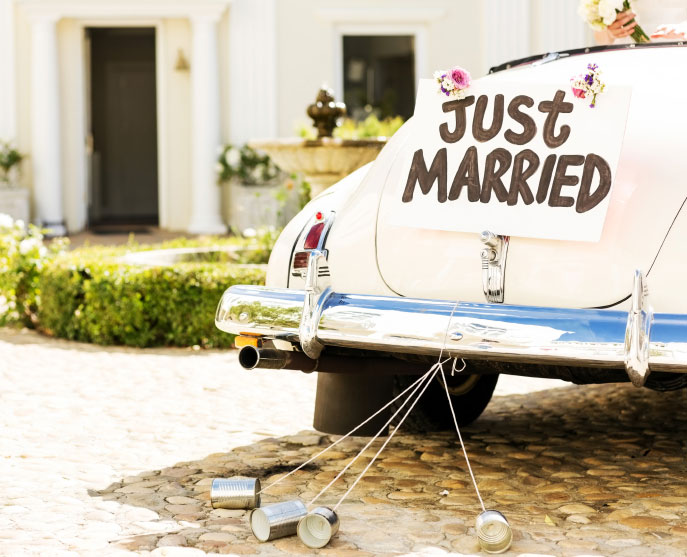 """A """"Just Married"""" sign hangs from a car at a wedding"""